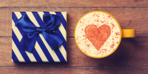 Auf einem Holztisch steht ein blau-weiß gestreiftes Geschenk mit blauer Schleife. Daneben steht eine mit Kaffee gefüllte Tasse, auf dessen Milchschaum ein Kakaoherz zu sehen ist.
